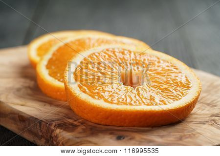 slices of ripe orange on olive cutting board