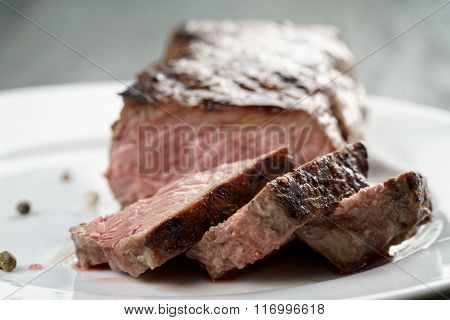 sliced beef steak on white plate close up