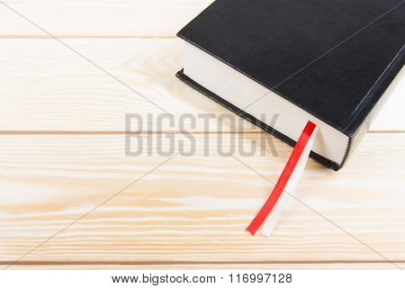 Black book with red and white bookmark on wooden table. Back to school. Copy space