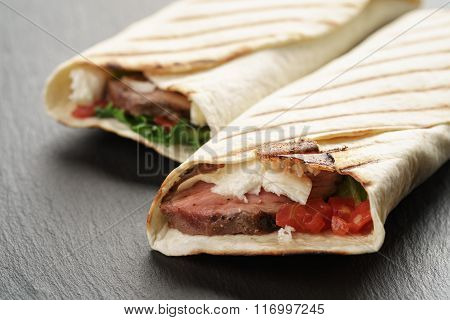 closeup photo of fresh homemade burritos with beef on slate board