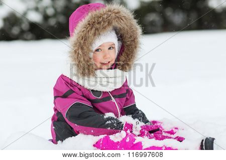 happy kid in winter clothes playing with snow