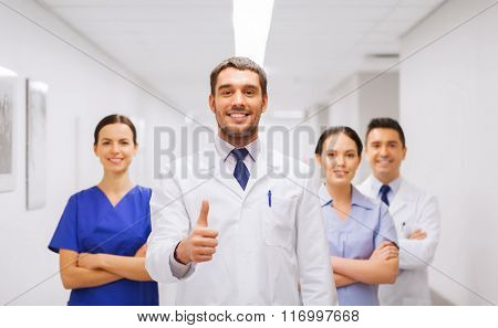 medics or doctors at hospital showing thumbs up