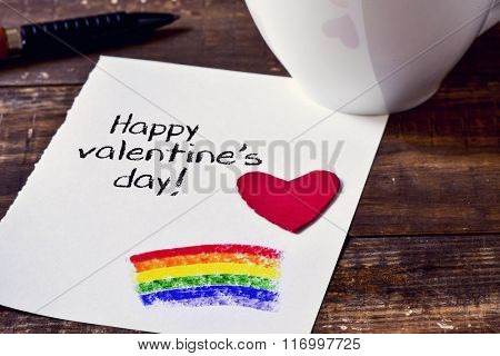 closeup of a note with the text happy valentines day handwritten in it and a rainbow painted in it, a red heart, a pen and a cup of coffee on a rustic wooden table