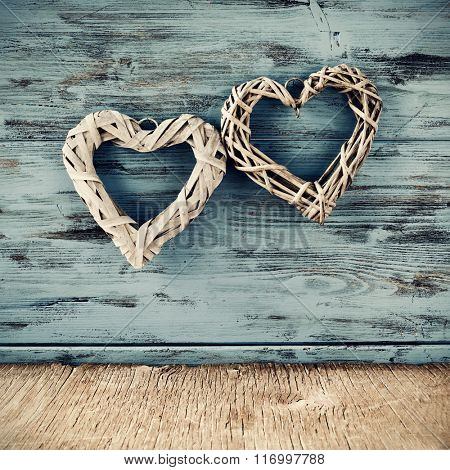 two heart-shaped ornaments made with natural fibers against a blue rustic wooden background