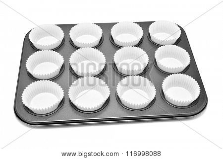 a baking tray with different holes for muffins or cupcakes, with some paper cups, on a white background