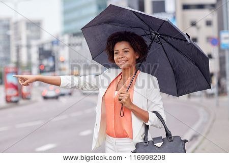 happy african woman with umbrella catching taxi