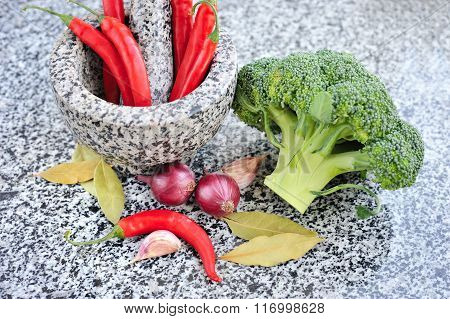 Stone Mortar And Pestle With Vegetables On A Granite Table