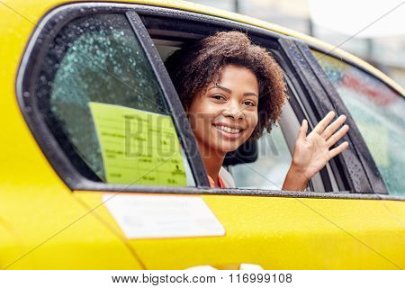 happy african american woman driving in taxi