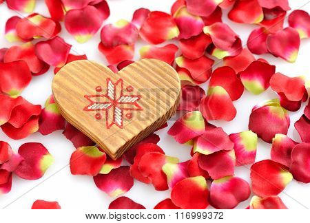 Wooden Heart On A Background Of Red Petals