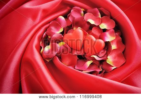 Two Hearts On A Background Of Red Petals And Satin