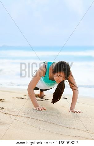 Teen Girl Exercising On Beach Near Blue Ocean Waters