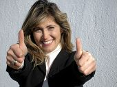 picture of thumbs-up  - smiling pretty business woman in suit giving thumbs up - JPG