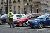 stock photo of mandate  - parking attendant traffic warden getting parking ticket parking ticket fine mandate - JPG