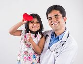 Постер, плакат: handsome pediatric doctor holding a baby girl male doctor with small girl indian doctor indian gi