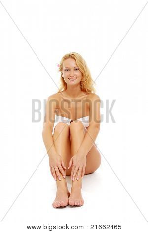 A portrait of smiling beautiful woman in a swimsuit sitting on the floor
