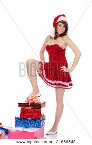 pretty young woman in red christmas clothing with present boxes on the floor, isolated on white