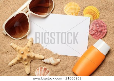 Sunglasses,sunblock and seashells with a blank card on sand.