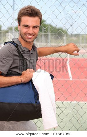 Smiling male tennis player with kitbag outside court