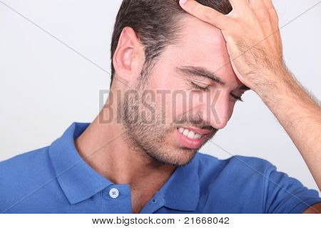 a 35 years old man taking his head with his hand, his face expresses failure