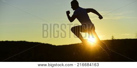poster of Silhouette of athlete running on sunset background copy space. Sportsman jogging in evening catching the sun. Man with sportive figure practices sport running for life. Sport and training concept.