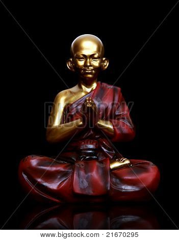 A religious spiritual golden monk statue praying over black