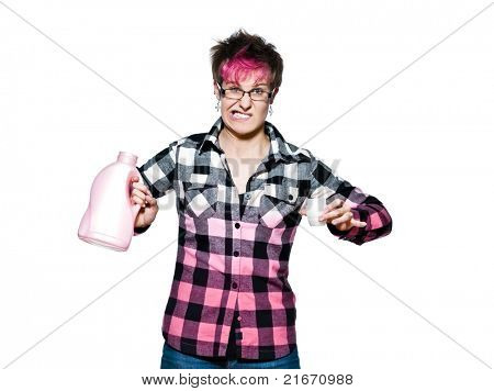 Trendy young woman with an angry expression holding detergent in studio on white isolated background