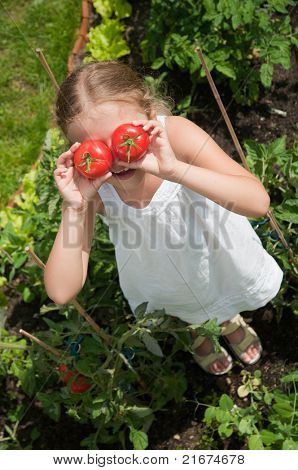 Vegetable garden - funny girl with fresh tomatoes