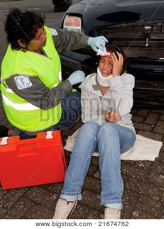 Female paramedic attending to a young car crash victim (the sleeve badges have been replaced by a non existing logo)