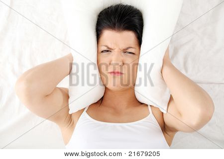 Female lying on bed and closing her ears with pillow.  Insomnia