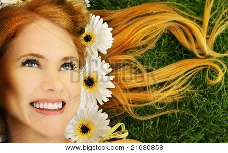 Close-up portrait of beautiful smiling young female with flowers in her hair laying in lush green grass