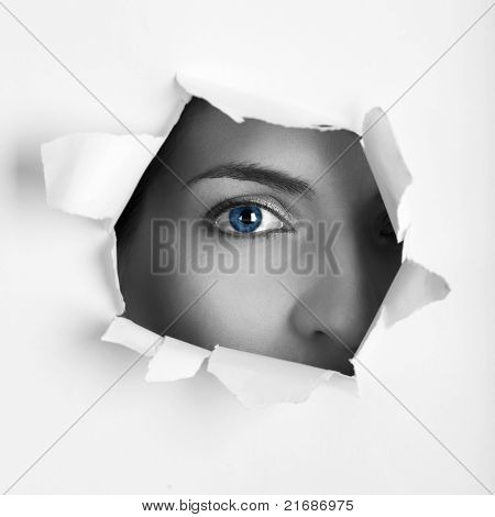 Beautiful female blue eye looking through a hole on a sheet of paper