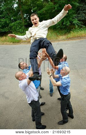A happy groom tossed into sky by a group of groomsmen