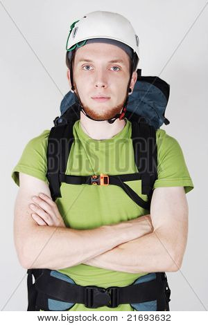 Mountain Tourist In Helmet And With Big Backpack Standing With Crossed Hands