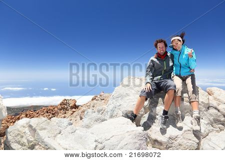Couple on mountain top of volcano Mount Teide, Tenerife after hiking to summit. Woman showing thumbs up success sign.
