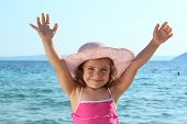 happy little girl with straw hat and hands up