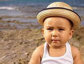 image of baby cowboy  - baby with a straw hat in the beach - JPG