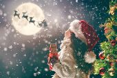 Merry Christmas! Cute little child with xmas present. Santa Claus flying in his sleigh against moon  poster