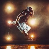 Young cool man break dancer jumping in club with lights and smoke. Tattoo on body. poster