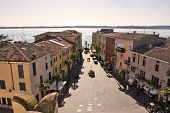 Aerial view on paved street among vintage houses and Lake Garda in Sirmione, northern Italy.