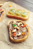 Delicious toast with chocolate paste and nuts on parchment poster