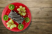 Dessert Of Cake And Fruit (grapes, Kiwi, Pomegranate) On A Wooden poster