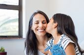 Young daughter kissing mother on cheek. Multiethnic little girl giving kiss to happy mother. Lovely  poster