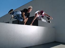 stock photo of parkour  - two male parkour freerunner jumping over a wall - JPG