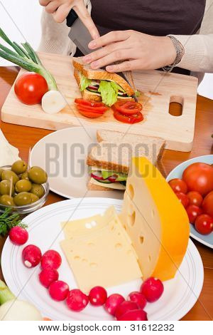 Table With Food And Woman Halving Sandwich
