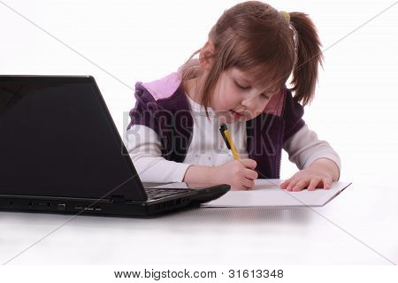 A Little Girl Sits Near The Notebook And Writes
