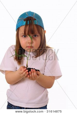 A Little Girl Stands And Holds A Plant In The Hands
