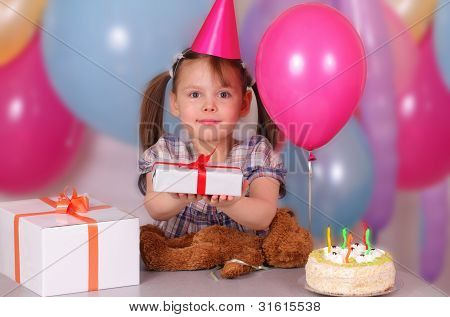 Happy Little Girl Holds A Gift On Her Birthday