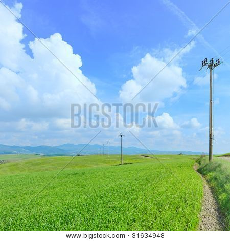 Electric Power Line, Green Field And Light Cloudy Blue Sky