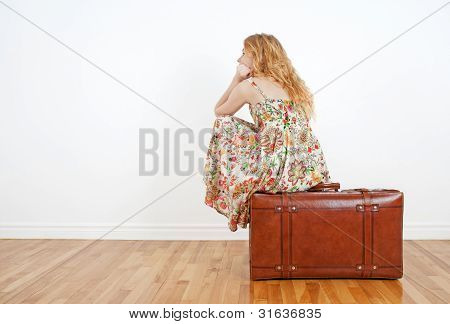 Girl Sitting On A Vintage Suitcase Anticipating Travel