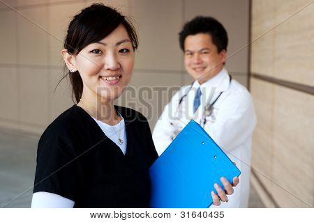 Asian Nurse With Doctor In Background